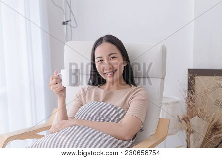 Beautiful Asian Woman Is Drinking Coffee Tea On A Sofa By The Windows