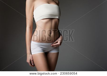 Close Up Of Slender Female Figure. Young Woman Is Standing In White Panties And Bandage Over Breast.