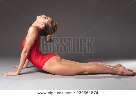 Side View Of Graceful Woman In Red Swimsuit Doing Cobra Asana With Calmness