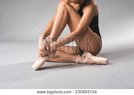 Slim Female Person In Swimsuit And Pointe Taking Rest With Calmness After Performing. Close Up
