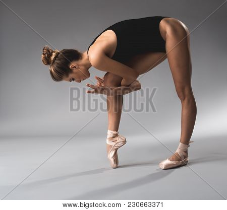 Full Length Of Calm Stretchy Fit Girl Hugging Her Leg, She Is Wearing Tricot And Ballet Shoes