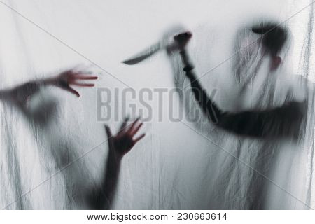 Silhouette Of Someone Holding Knife And Murdering Victim, Crime Concept