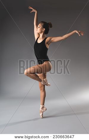 Full Length Of Fit Woman Wearing Black Maillot Balancing On Tips Of One Leg With Eyes Closed