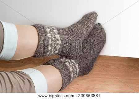 Pair Of The Thick Gray Wool Hand-knitted Socks On Women Legs On The Wooden Floor On A Light Colored