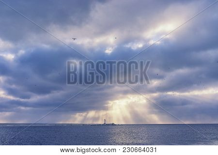 A Beacon Under The Rays Of The Sun Through The Clouds Against The Background Of A Flock Of Birds And