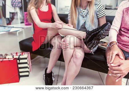 Cropped Image Of Teen Girls Sitting On Bench Relaxing After Shopping In Clothing Store. Young Stylis