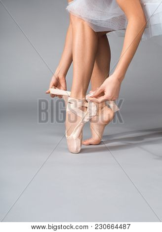 Close Up Of Ballerina Arms Wearing Her Ballet Shoes And Tying Ribbons On It
