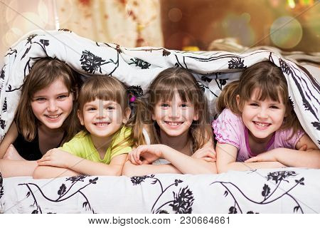 Funny Little Sisters Hides Under A Blanket. Cute Girls Having Fun On The Bed. Concept Of Kids Sleep,