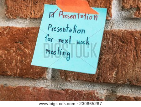 Closeup of sticky note on brick wall