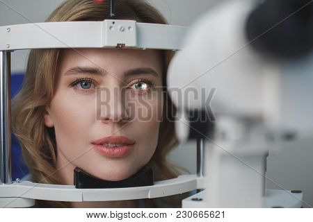 Portrait Of Close Up Concentrated Female Face Examining Eyesight With Equipment In Hospital. Optomet