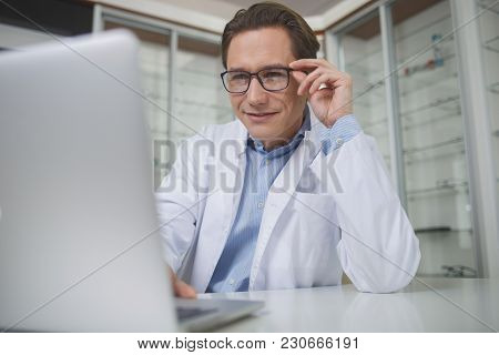 Portrait Of Smiling Doctor Typing In Notebook Computer While Sitting At Table Indoor. Specialist Dur