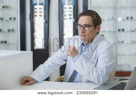 Portrait Of Pensive Smart Ophthalmologist Sitting At Desk In Optician Shop. Clinic Concept