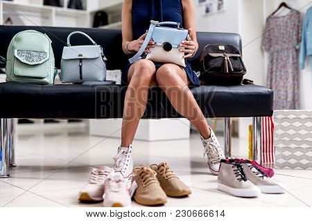 Portrait Of Young Smiling Female Shopper Sitting With A New Handbag On Her Laps In Accessories Shop.