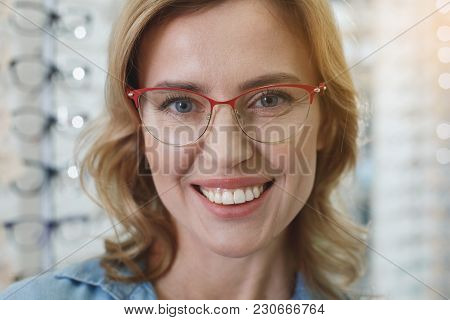 Portrait Of Woman Wearing Spectacles While Expressing Happiness In Optician Shop. Ophthalmology Conc