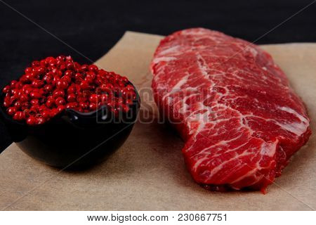 fresh raw beef meat marble steak on paper with saucer full pink peppercorn spice over black wooden table
