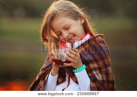 Girl With A Cup Of Hot Cocoa Wrapped In A Blanket Sitting On A Bench In The Cool Autumn Day.the Phot