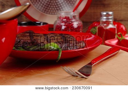 red theme lunch : fresh grilled bbq roast beef steak on red plate with green chili tomato soup ketchup sauce and modern cutlery served on wooden plate over table