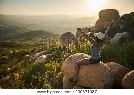 fit female hiker sitting on rock at mountain top looking at city in distance with arms up happy with accomplishment at sunset