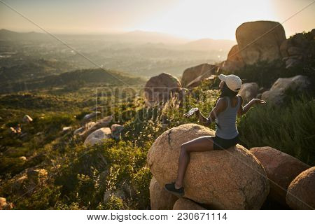 fit female hiker meditating on top of mountain at sunset