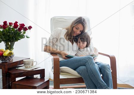 Mother,reading A Book To Her Child, Sitting In Rocking Chair, Bouquet Of Roses On The Table