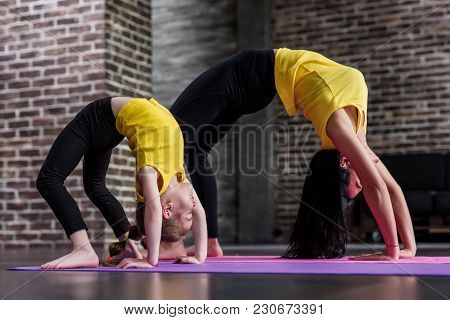 Kids Yoga Female Teacher Training A Child Girl Standing In Wheel Pose Working Out In Stylish Sports