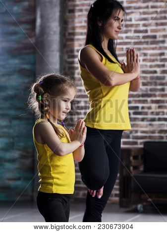 Mother And Daughter Wearing Sports Clothing Practicing Yoga Together Meditating Standing On One Leg