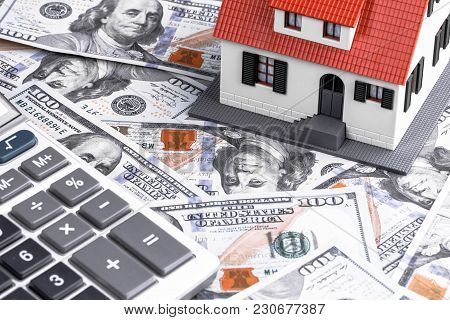 Close-up Of A House Model With Calculator On Dollar Notes. Mortgage Concept
