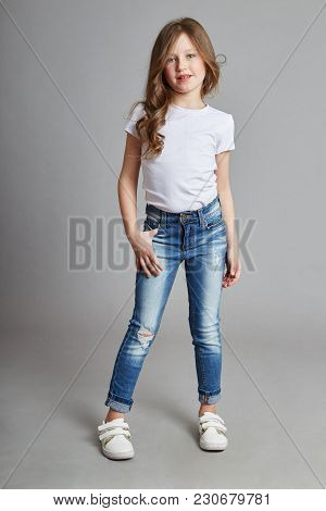 Little Girl With Long Blonde Hair And In Jeans Posing On A White Background. Joy Fun, Young Model Ki