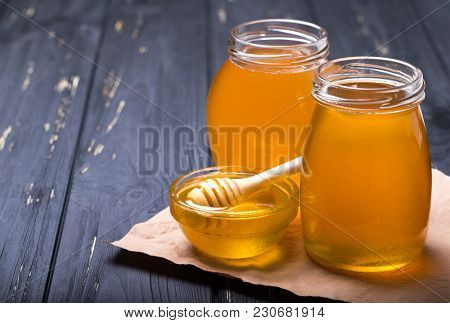 Honey with wooden honey dipper on wooden table