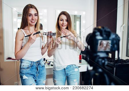 Two Beauty Bloggers Filming A Makeup Shopping Guide Demonstrating Eyeshadows And Brushes Against Mak