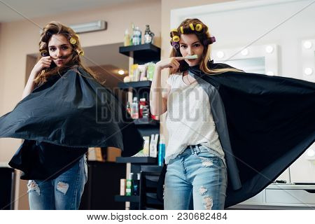 Two Female Friends Goofing Around In Front Of The Camera Making Moustache From Hair And Curler Stand
