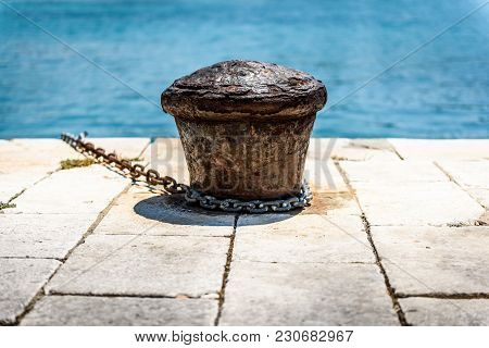 Old Rusty Steel Mooring Bollard Pole On A Pier. The Best Way For Boat Or Ship Mooring In Harbor. Cro