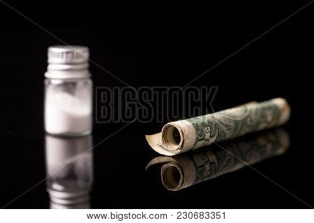 Cocaine Or Other Illegal Drugs That Are Sniffed By Means Of A Tube, Isolated On Black Glossy Backgro
