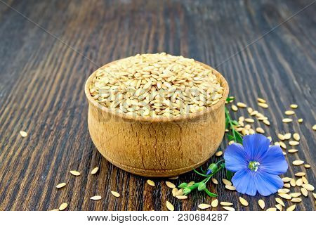 Linen Seeds White In A Bowl And Blue Flax Flower On A Background Of A Dark Wooden Board