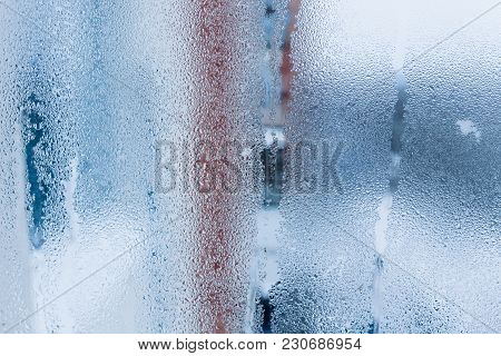 Background of natural water condensation, window glass with high air humidity, large drops drip. Col