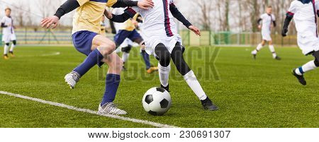 Two Youth Footballers Running The Ball. Junior Football Match. Boys Boys Playing Soccer Match On Pro