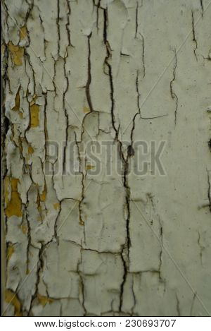 Close View Of Peeling Paint On An Old Yellow Wooden Wall