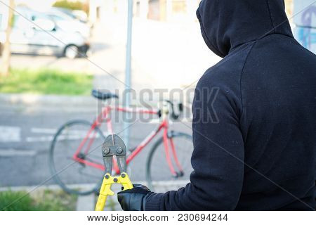 Thief Stealing A Parked Bike In The City Street