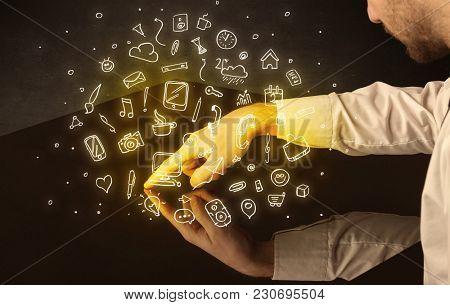 Male hands touching interactive table with yellow mixed media icons on it