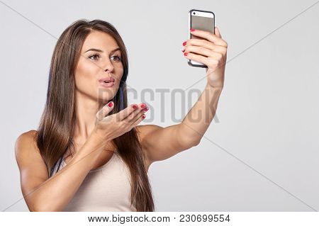 Closeup Of Beautiful Smiling Brunette Woman Taking Self Portrait On Smart Phone Sending A Kiss, Over