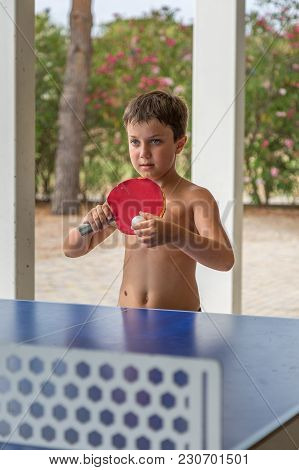 Ten Year Boy Playing Table Tennis Shirtless In The Park-