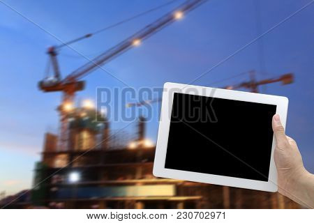 hand hold digital tablet with Scaffolding construction site at dusk with moving crane