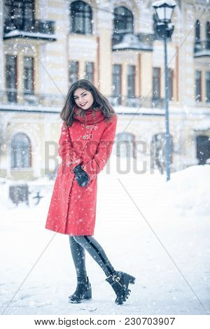 Young Woman Stands Alone On The Street. Snowing