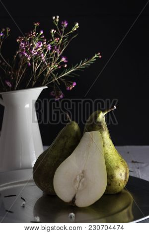 In The Image We See Two Green Pears, And Half Of Another Pear,which Are On A Silver Plate; Behind Th