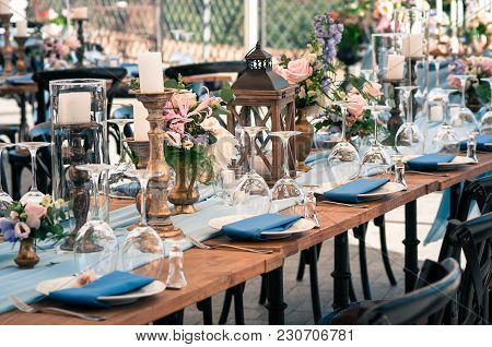 Wedding Or Other Catered Event Setting, Flowers, Candles, White Plates, Blue Napkins, Wooden Tables,