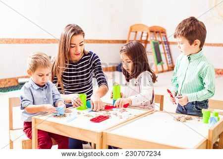 Babysitter And Children Play With Kinetic Sand In The Daycare