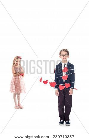 Adorable Smiling Little Girl Tying Stylish Boy With Rope And Red Hearts Isolated On White