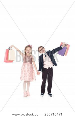 Adorable Little Kids Holding Shopping Bags And Smiling At Camera Isolated On White