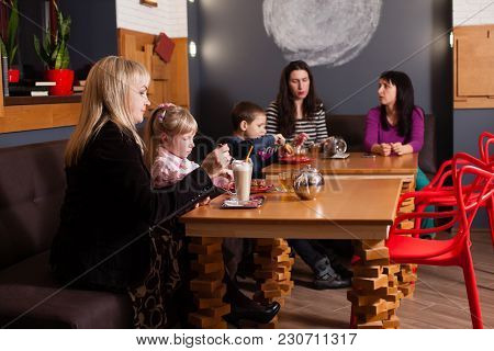 A Group Of Friends Having The Beverages With The Kids Sitting Nearby. Horizontal Indoors Shot.