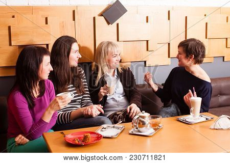 Girlfriends Discussing The Latest News During The Informal Meeting In Cafe